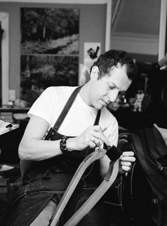 Fabien Ifirès, artisan d'art, sellier, cousant une manchette avec les outils traditionnels dans sont atelier à Paris. Photographe : Maxime Sery.