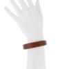 Bracelet fin minimaliste mettant en valeur le travail de couture à la main, le point sellier, réalisée dans notre atelier à Paris, en cuir marron.
